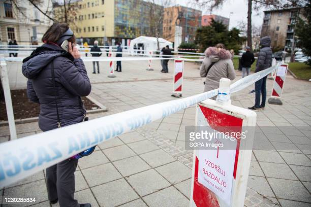 People keep a safe distance while waiting in a line to take a COVID-19 rapid antigen test as Slovenia begins mass testing. COVID-19 rapid antigen...