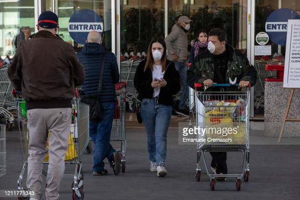 People keep distance as a safety measure against the spread of the novel coronavirus as they line up to shop at a supermarket on March 11 2020 in...