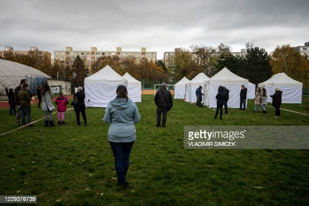 People keep distances as they wait for the result of test for the novel coronavirus COVID-19 during nationwide testing in Bratislava, Slovakia on...