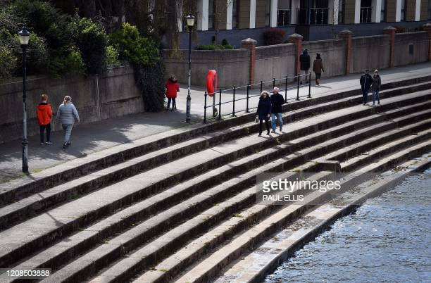 People keep social distancing gaps between them as they walk along the embankment of the River Trent in Nottingham central England on March 29 as...