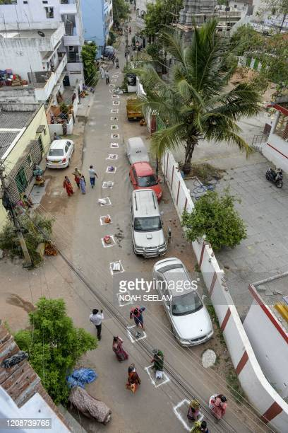 People keep their bags inside marked areas on a street as they wait to receive free rice distributed at a government store during a...