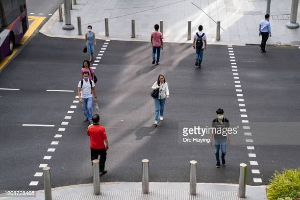 People keep their distance apart from each other while crossing a traffic junction on Orchard Road on March 31 2020 in Singapore The Singapore...