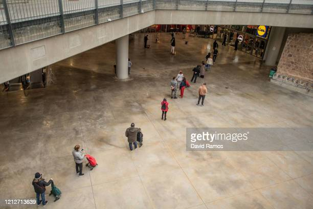 People keep their distance as they wait their turn in a queue to access a Lidl supermarket at the Sant Antoni green market on March 16 2020 in...
