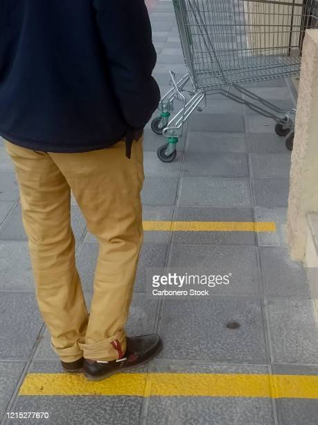 people keep their distance as they wait their turn in a queue to access a supermarket - tokyo stock price index stock pictures, royalty-free photos & images