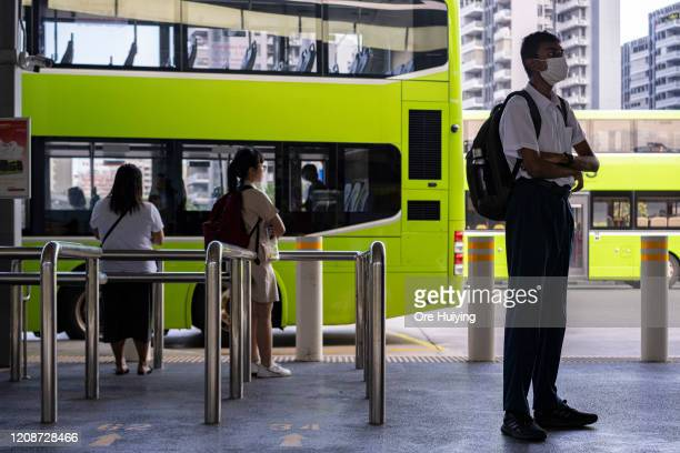 People keep their distance from each other while waiting for buses at a bus interchange on March 31 2020 in Singapore The Singapore government has...