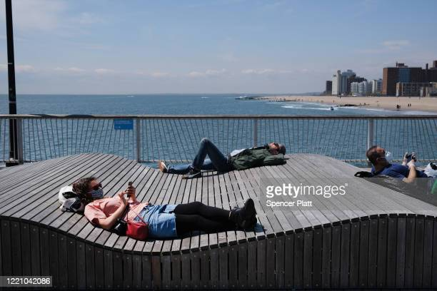 People keep their personal distance as they enjoy a spring afternoon at Brooklyn's Coney Island on April 25 2020 in New York City New York City which...