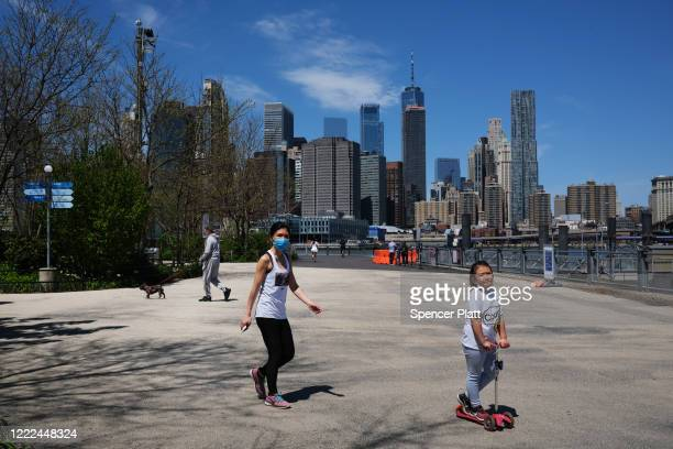 People keep their personal distance as they enjoy a spring afternoon in Brooklyn Bridge Park on May 02, 2020 in the Brooklyn borough of New York...