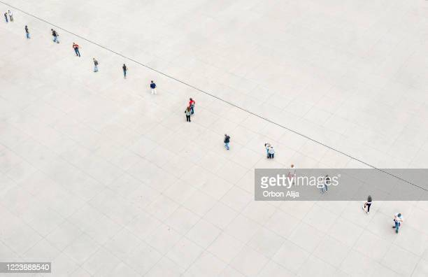 people keeping a safe distance while waiting in line for covid-19 - avoidance stock pictures, royalty-free photos & images