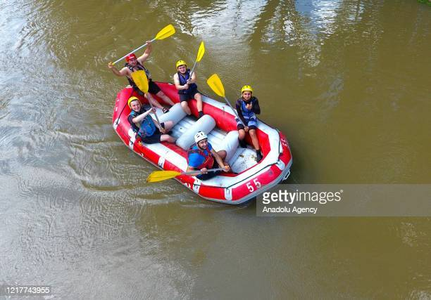 People keeping their social distance ride in inflatable boats as they are rafting down the Melen stream in Duzce Turkey on June 1 2020