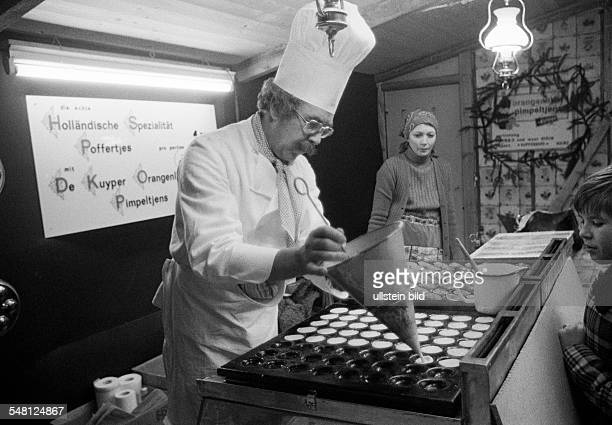 people kermess funfair gourmet stall cook with chefs hat prepares to bake sweet cookies and cakes Poffertjes are a speciality from the Netherlands...