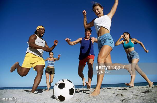 People kicking a soccer ball around on the beach
