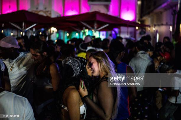 People kiss and dance on Ocean Drive in Miami Beach, on March 22, 2021. - The US city of Miami Beach, overrun by crowds of spring break tourists...