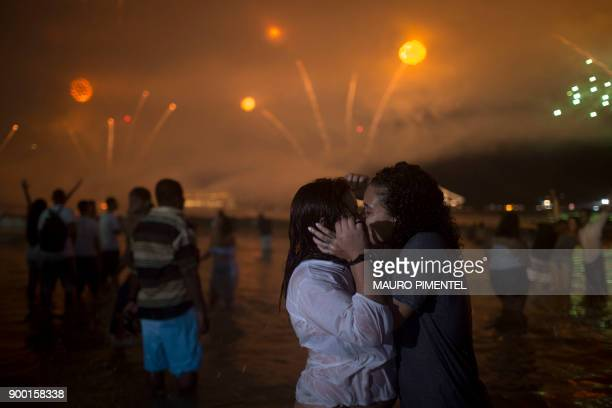 People kiss as fireworks go off during New Year's celebrations at Copacabana beach in Rio de Janeiro on January 1 2018 / AFP PHOTO / MAURO PIMENTEL
