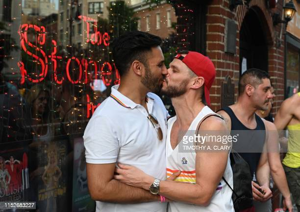 People kiss as they gather for the 50th anniversary of the Stonewall Riots in front of the Stonewall Inn in New York, June 28, 2019. - The June 1969...