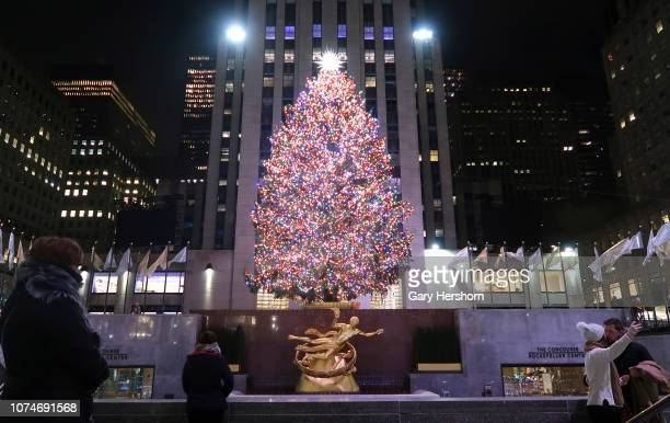 People kiss as they take a selfie in front of the Christmas tree in Rockefeller Center before sunrise on November 29 2018 in New York City