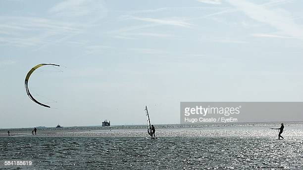 People Kiteboarding And Windsurfing In Sea Against Sky