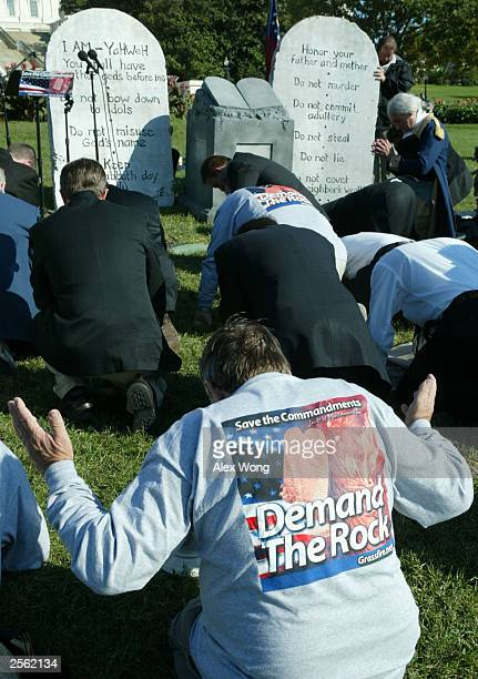 People kneel and pray in front of a display of a representation of the Ten Commandments October 5 2003 during a rally at the West Lawn of the US...