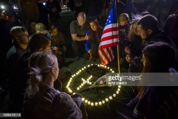People kneel around lit candles during a vigil to pay tribute to the victims of a shooting in Thousand Oaks California on November 8 2018 A 28yearold...