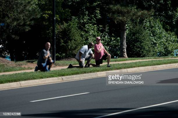 People kneel as a motorcade with US President Donald Trump passes after leaving the Trump National Golf Club September 2 2018 in Sterling Virginia