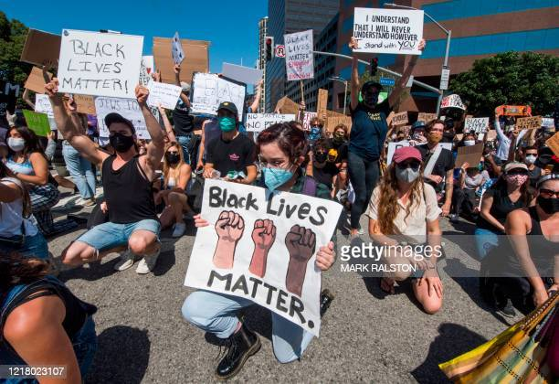 People kneel as protesters and supporters of Black Lives Matter block an intersection outside the Federal Building on busy Wilshire Blvd as they...