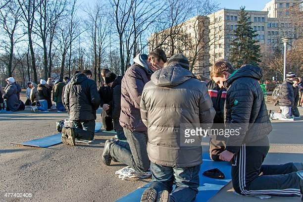 People kneel as they pray on Liberty Square in the northeastern Ukrainian city of Kharkiv early on March 9 2014 More and more believers of different...