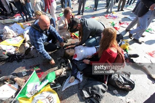 People kneel beside a victim following an explosion at the main train station in Turkey's capital Ankara on October 10 2015 At least 30 people were...