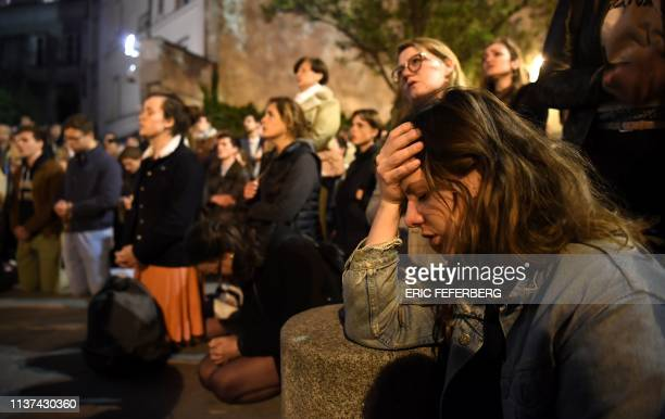 TOPSHOT People kneel on the pavement as they pray outside watching flames engulf NotreDame Cathedral in Paris on April 15 2019 A colossal fire swept...