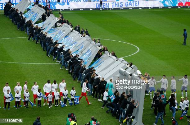 People knock over a mock-up of the former Berlin Wall during a performance prior to the German first division Bundesliga football match Hertha BSC...