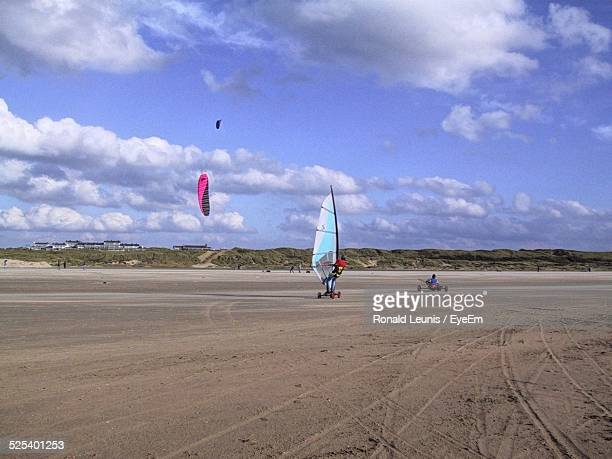 People Land Sailing On Beach Against Sky