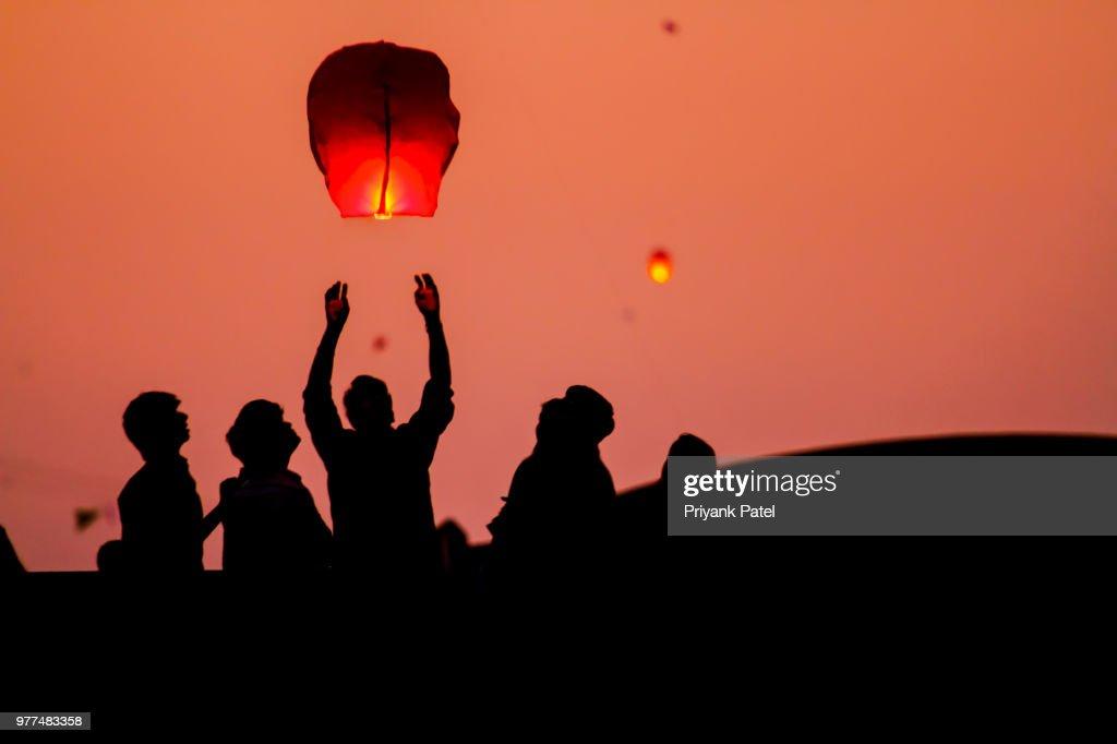 People launching chinese lanterns, Gujarat, India : Stock Photo