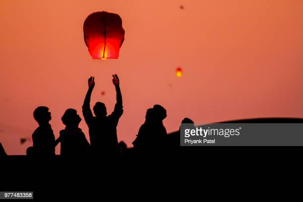people launching chinese lanterns, gujarat, india - lantern stock photos and pictures