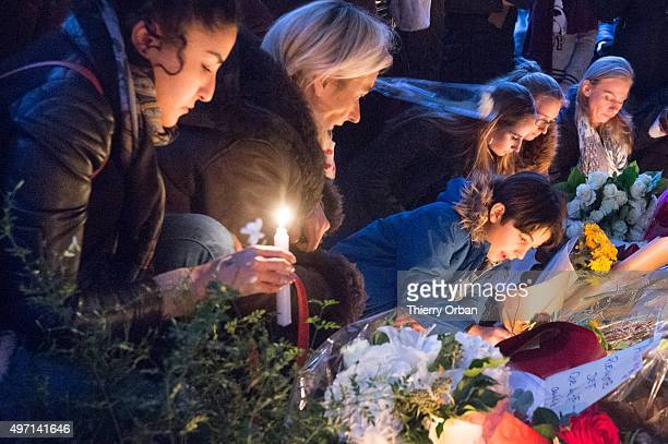 People lay candles and flowers in front of 'the belle epoque' on Charonne street near the restaurant site of yesterday's attacks on November 14 2015...