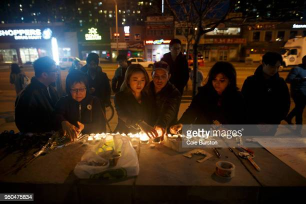 People lay candles and leave messages at a memorial for victims of a crash on Yonge St at Finch Ave after a van plowed into pedestrians on April 23...