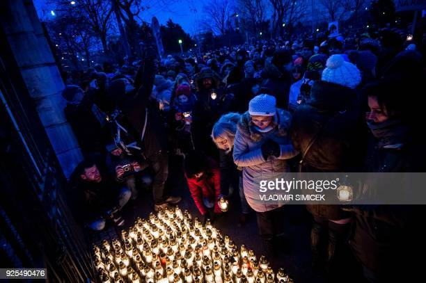 TOPSHOT People lay candles in front of the government office during a silent protest march in memory of Murdered Slovak journalist Jan Kuciak and his...