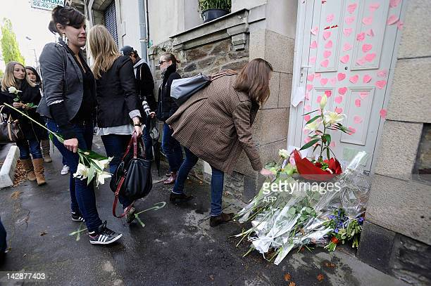 People lay down flowers in front of the Dupont de Ligonnes family's house as part of a silent march on April 14 2012 in the streets of Nantes western...