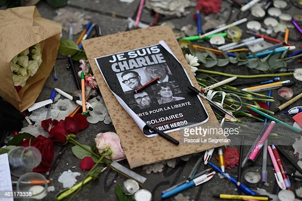 People lay flowers and candles at the Place de la Republique at midday in solidarity with victims of yesterday's terrorist attack on January 8 2015...