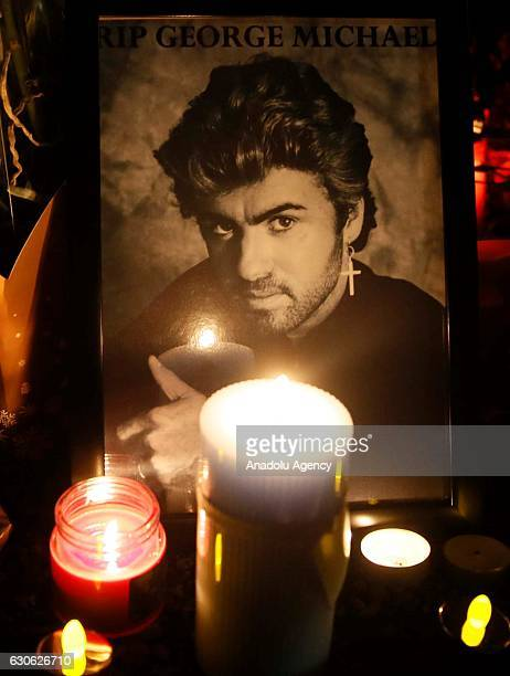 People lay flowers and light candles in the memory of British singer George Michael who died of heart failure at his Oxfordshire home aged 53 outside...