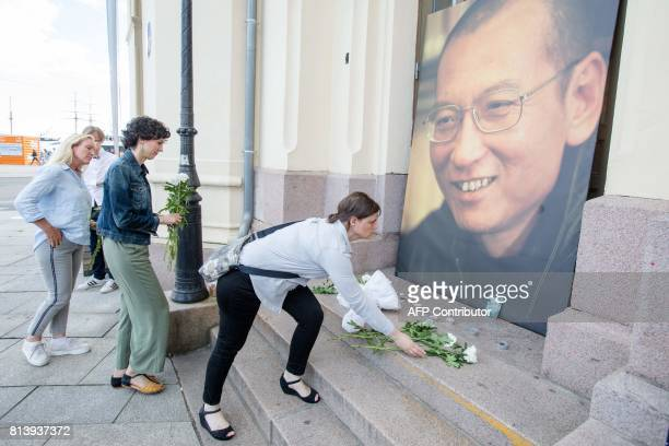 People lay flowers and light candles infront of a photo of Nobel peace laureate Liu Xiaobo who died July 13 2017 outside the Nobel´s Peace center in...