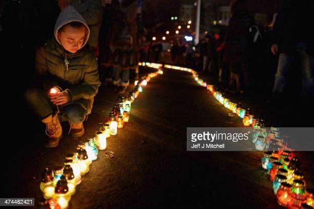 People lay flowers and pay their respects at a memorial for antigovernment protesters killed in clashes with police in Independence Square on...