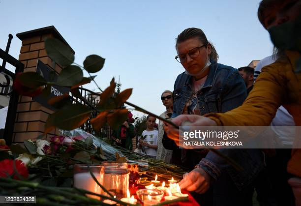 People lay flowers and place candles at a makeshift memorial for victims of the shooting at School No. 175 in Kazan on May 11, 2021. - At least nine...