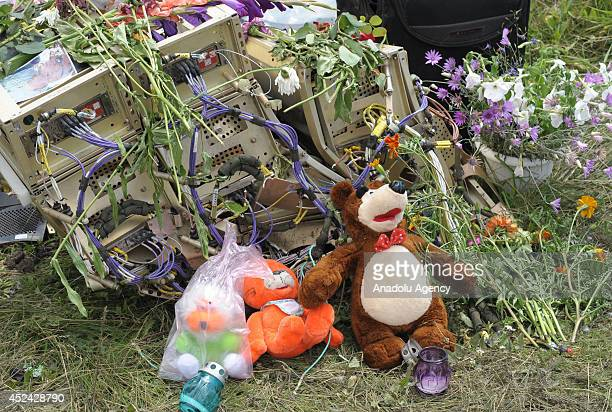 People lay flowers and put toys belong child passengers died in crash upon the wreckages of plane as search and rescue specialists inspect at the...