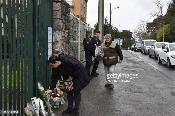 People lay flowers as gendarmes stand guard in front of the Gendarmerie Nationale in Carcassonne on March 24 2018 in tribute to the gendarme killed...