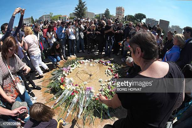 People lay flowers as they gather to pay their respects during a ceremony on April 24 2015 at the Memorial of the Armenian Genocide in Marseille as...