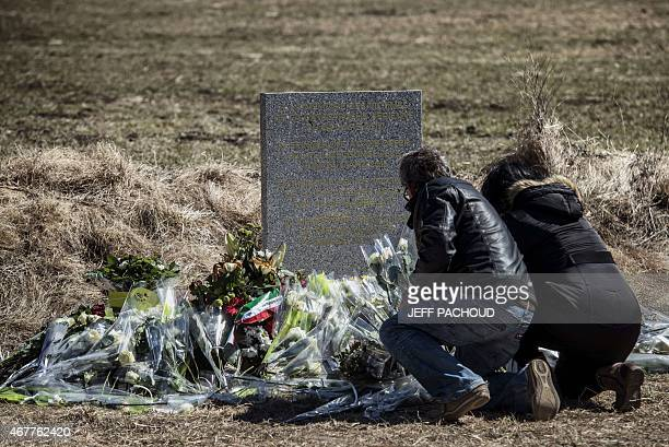 People lay flowers as they pay tribute in front of a stele carved in French German Spanish and English in memory of the victims of the Germanwings...