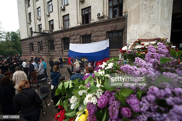 People lay flowers at a Christian icon set under a Russian flag outside the burned trade union building in the southern Ukranian city of Odessa on...