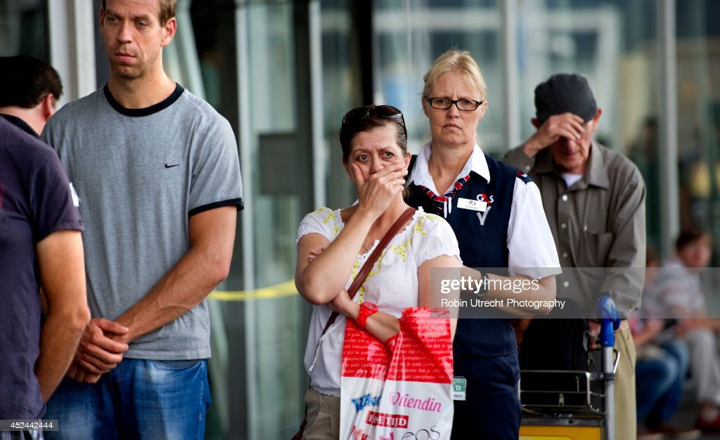 People lay flowers at a makeshift memorial for the passengers aboard doomed flight Malaysia Airlines MH17 at Schiphol Airport July 20, 2014 in Amsterdam, the Netherlands. Flight MH17 was travelling from Amsterdam to Kuala Lumpur when it crashed killing all 298 on board including 80 children. The aircraft was allegedly shot down by a missile and investigations continue over the perpetrators of the attack.