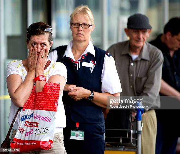 People lay flowers at a makeshift memorial for the passengers aboard doomed flight Malaysia Airlines MH17 at Schiphol Airport July 20 2014 in...