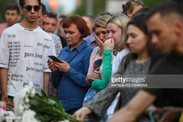 People lay flowers at a makeshift memorial for victims of the shooting at School No. 175 in Kazan on May 11, 2021. - At least nine people, most of...