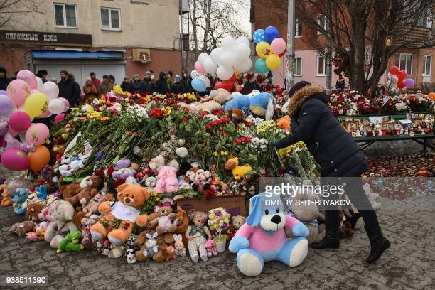 People lay flowers at a makeshift memorial in tribute to the victims of a fire at a shopping centre in Kemerovo on March 27 2018 Russian authorities...