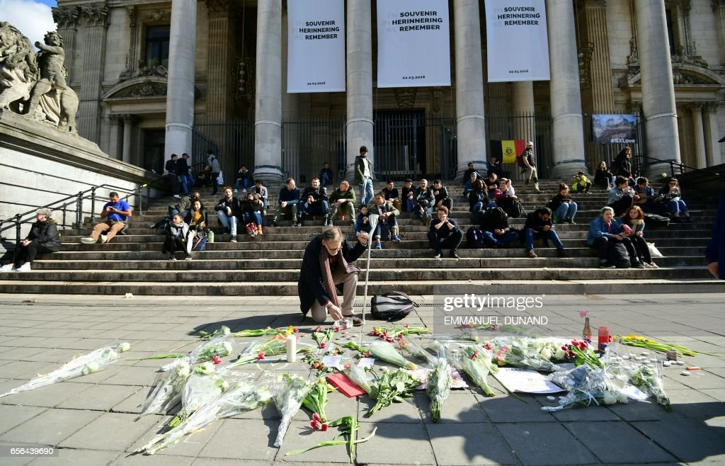 TOPSHOT - People lay flowers at a make-shift memorial under commemorative banners as Belgium marks the first anniversary of the twin Brussels attacks by Islamic extremists on March 22, 2017 at La Bourse in Brussels. Belgium marks the first anniversary of the Islamic State bombings in Brussels, one at the airport and the other in the metro, in which 32 people were killed and more than 320 wounded with ceremonies showing that the heart of Europe stands defiant. / AFP PHOTO / Emmanuel DUNAND
